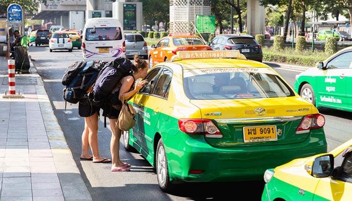 Saccopelisti mentre parlano con un tassista a Bangkok